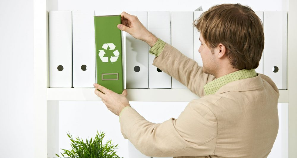 7129869 - man drawing out green folder with recycling symbol in office.